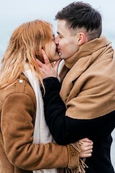 Вид сбоку молодой пары, целующейся зимой