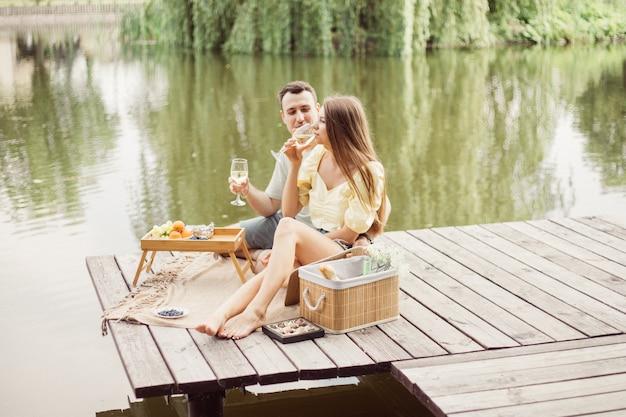 강이나 호수 근처에서 낭만적인 피크닉을 즐기는 젊은 부부의 모습