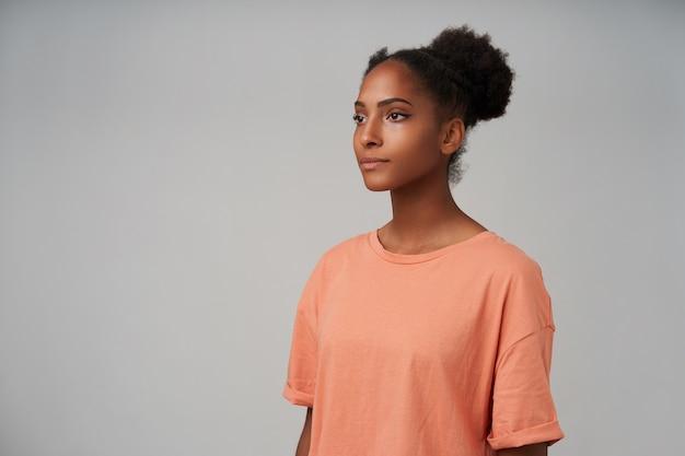 落ち着いて前方を見て、カジュアルな服を着て灰色の上に立っている間手を下に保つ若い暗い肌の巻き毛の女性の側面図