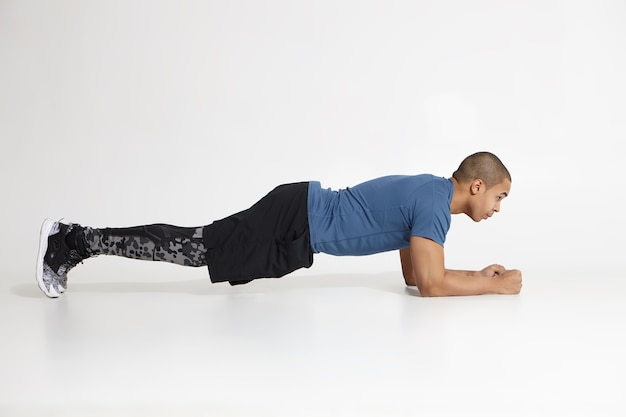세련 된 운동화와 훈련 옷을 입고 스튜디오에서 팔꿈치 판자를 하 고 젊은 어두운 피부 스포츠맨의 측면보기, 결정된 집중된 표현으로 그를 앞두고. 지구력과 체력