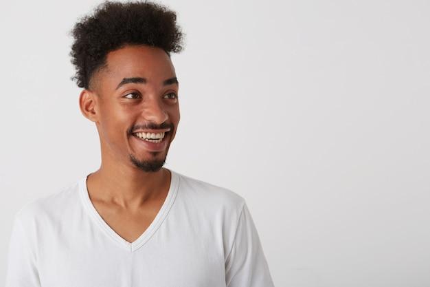 넓게 웃고있는 흰색 기본 티셔츠를 입은 젊은 어두운 피부의 면도하지 않은 남자의 측면보기