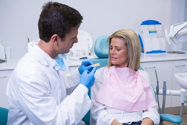 患者に歯科用カビを示す若い医師の側面図