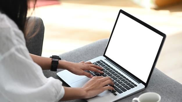 소파에 편안하고 집에서 거실에서 컴퓨터 노트북을 사용하는 젊은 여성 프리랜서의 측면보기