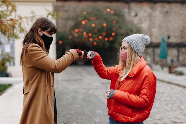 屋外で会ったときに拳でぶつかる医療用保護マスクの若い女性の友人の側面図。距離でお互いに挨拶する美しい女性。