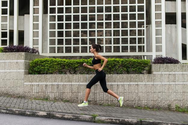 音楽を聴くと町の歩道でジョギングする若い女性ランナーの側面図