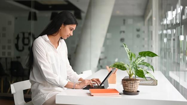 現代のオフィスで白いテーブルの上のコンピュータータブレットで作業している若い女性の側面図。