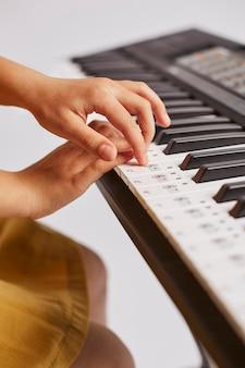 Молодая девушка учится играть на электронной клавиатуре, вид сбоку