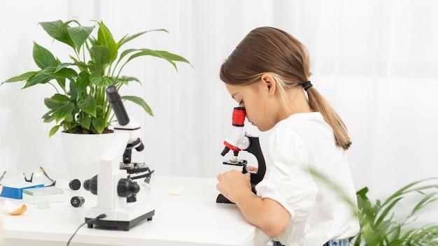 Вид сбоку молодой девушки, глядя в микроскоп