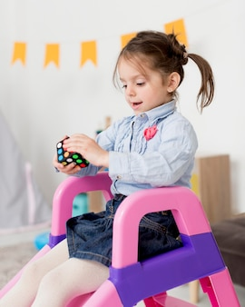 Вид сбоку молодая девушка на слайде, держа кубик рубика