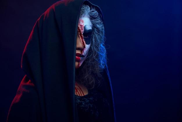 Вид сбоку молодая девушка с косметикой черепа в черной мантии