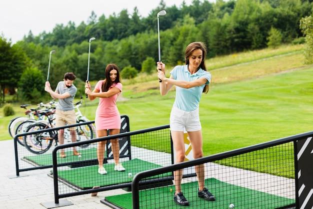 Вид сбоку молодых гольфистов, практикующих