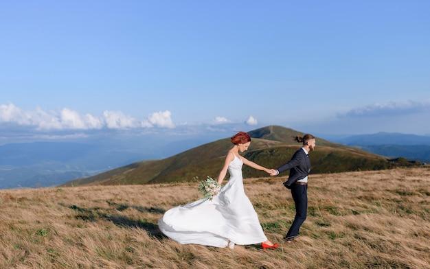 야외에서 걷는 흰 드레스에 빨간 머리 소녀와 젊은 남자의 측면보기