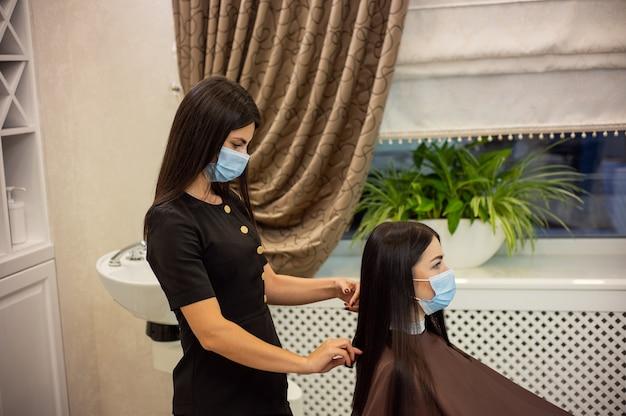 パンデミック時の美容院で若い美容師と顧客の側面図