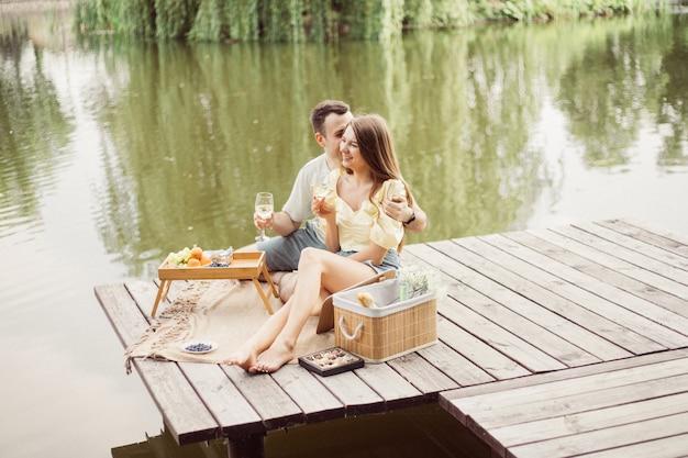 강이나 호수 근처에서 낭만적인 피크닉을 하는 젊은 행복한 커플의 옆모습, 야외에서 함께 와인을 마시는 여성과 남성, 여름 휴가를 즐기는 사람들