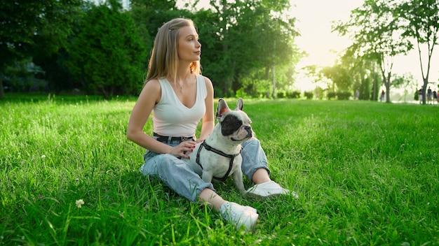 かわいい白と茶色のフレンチブルドッグと新鮮な草の上に座っている若い幸せな女性の側面図。夏の夕日を楽しむゴージャスな笑顔の女の子、都市公園で犬をかわいがります。人間と動物の友情。