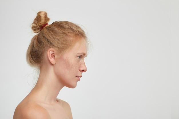 落ち着いた顔で自分の前を見て、白い背景の上に隔離された彼女の唇を折りたたんでいるカジュアルな髪型の若い素敵な赤毛の女性の側面図