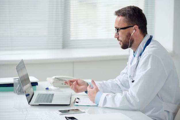 Вид сбоку на молодого врача-мужчину в whitecoaat и наушниках, слушающего онлайн-пациента и дающего медицинские советы, сидя перед ноутбуком