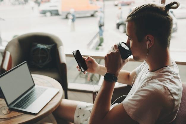 노트북과 둥근 나무 테이블에 앉아 이어폰에 가벼운 여름 옷을 입은 젊은 남성의 측면보기