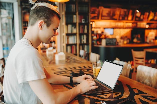 高い木製のテーブルの窓に座って、ノートパソコンのキーボードの笑顔で入力して白いシャツの創造的なヘアカットを持つ若い男性の側面図