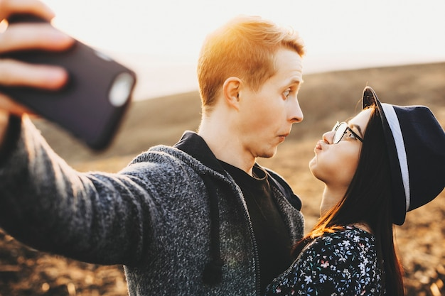 젊은 남자와여자가 재미있는 얼굴을 만들고 아름 다운 자연의 배경에 셀카를 복용하는 동안 서로보고의 측면보기 시골에서 셀카를 위해 찡그린 재미있는 커플