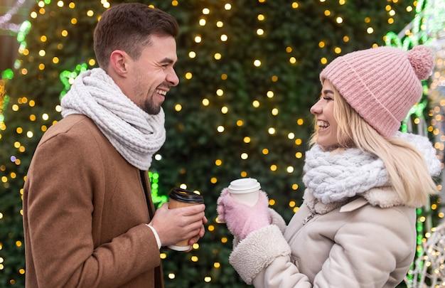 クリスマスの日にクリスマスツリーの近くに立っている間、笑顔でお互いを見つめながら、ホットドリンクのテイクアウトカップと若い男性と女性の側面図