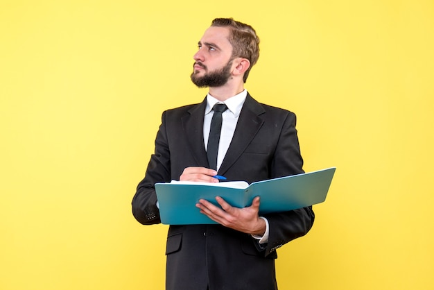 Вид сбоку бизнесмена молодого человека, смотрящего вверх и думая, указывая ручкой на синюю папку на желтой стене