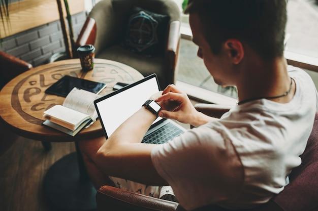 Вид сбоку молодого человека, проверяющего умные часы во время работы за ноутбуком в кафе