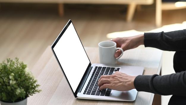 リビングルームに座っているときにコンピューターのタブレットで入力する若い男の手の側面図。