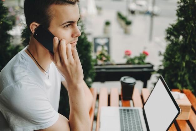 空白の画面とスマートフォンの会話をしている現代のラップトップの近くの屋外カフェに座っているカジュアルな服装の若い男の側面図