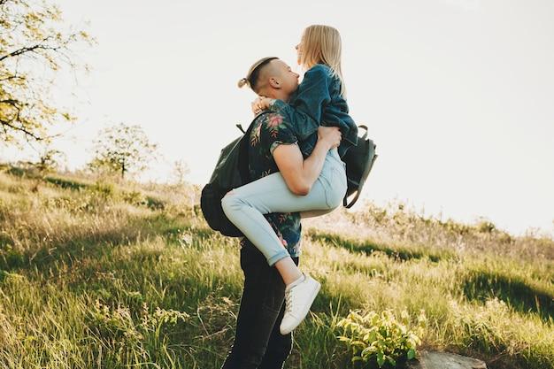 Вид сбоку на молодого человека в повседневной летней одежде, держащего в руках счастливую привлекательную белокурую женщину, обнимающую его на ярко-зеленом, залитом солнцем травянистом холме