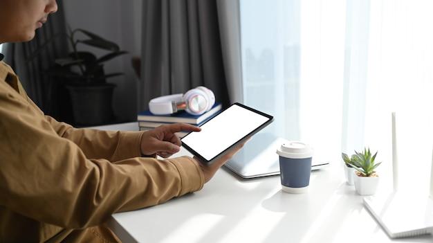 Вид сбоку молодого человека, сидящего на удобном рабочем месте и использующего цифровой планшет во время работы в интернете.