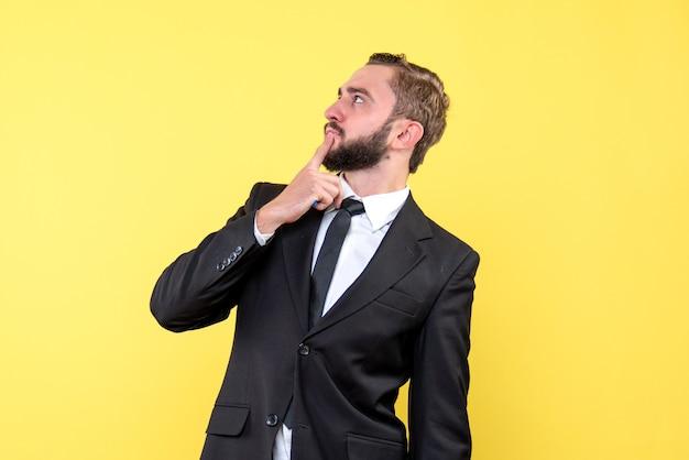 黄色い壁のあごに人差し指を押す若い男の思いやりのあるビジネスマンの側面図