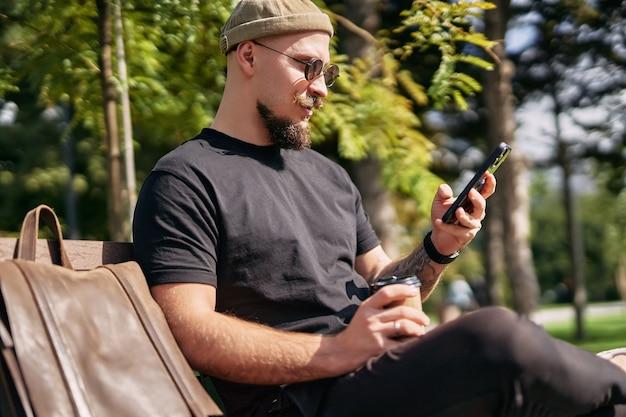 캐주얼 옷을 입은 청년의 옆모습은 야외에서 스마트폰을 서핑하는 동안 벤치에 앉아 있다