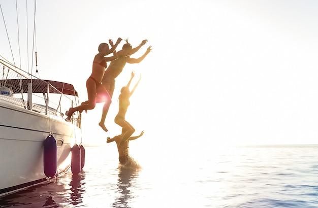Вид сбоку на молодых друзей-миллениалов, прыгающих с парусной лодки в морское путешествие по океану