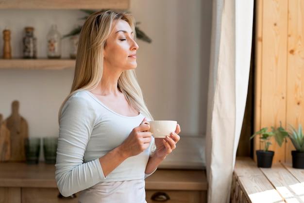 一杯のコーヒーを楽しんでいる若い母親の側面図