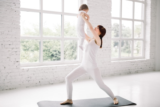 흰 벽과 큰 창문 배경 위에 그녀의 아기와 함께 젊은 어머니 운동의 측면보기. 어머니는 재미와 그녀의 아기와 함께 연주.