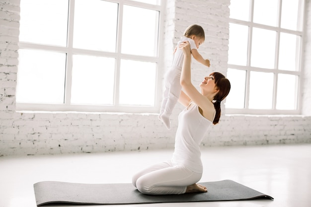 큰 라이트 룸에서 검은 매트에 앉아 그녀의 아기와 함께 젊은 어머니 운동의 측면보기. 어머니는 재미와 그녀의 어린 소녀와 놀고