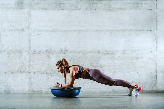Вид сбоку молодой мускулистой кавказской спортивной брюнетки в спортивной одежде с хвостиком, делающим доски и опирающимся на мяч bosu.