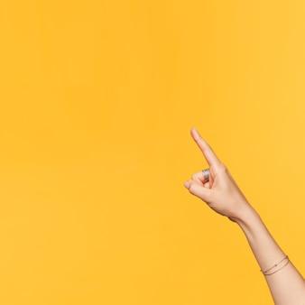 노란색 배경 위에 절연 검지 손가락으로 위쪽으로 가리키는 동안 발생하는 액세서리와 함께 젊은 예쁜 손의 측면보기. 신체 언어 개념