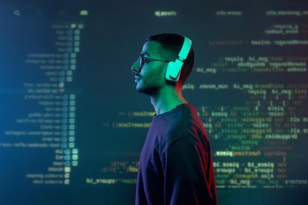 デコードされた情報で画面に立っているヘッドフォンとカジュアルウェアの若いプログラマーの側面図