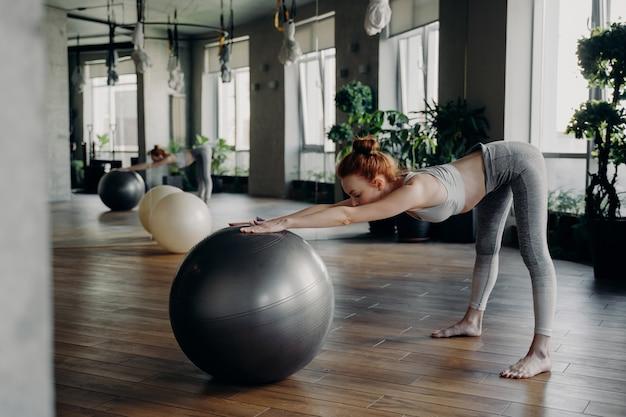 거울이 있는 아름다운 피트니스 스튜디오에서 스트레칭 운동을 하는 동안 활동적인 옷을 입은 젊은 날씬한 여성의 측면, 맨발로 바닥에 단단히 서서 피트볼로 운동하는 여성