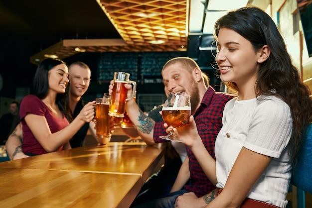 행복 한 친구와 함께 자유 시간을 즐기고 바에서 맥주를 마시는 젊은 미소 갈색 머리의 측면보기. 술을 마시고 술집에서 이야기하고 웃고있는 쾌활한 회사. 음료와 재미의 개념.