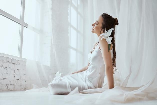 Вид сбоку молодой улыбающейся брюнетки женщины, сидящей на полу и держащей цветок лилии на плече. портрет девушки с мокрыми волосами, позирует на белом фоне и глядя в окно. понятие красоты.