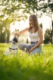 都市公園でフレンチブルドッグを訓練している若い笑顔の女性の側面図。純血種のペットの匂いが女性の犬の飼い主の手からおやつ、背景に美しい夏の夕日。動物調教の概念。