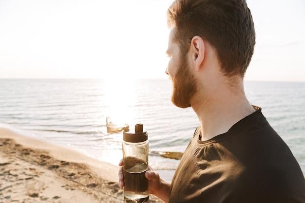水のボトルを保持している若いスポーツマンの側面図