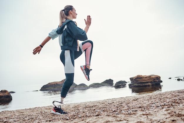 義足を持つ若いスポーティな障害のある女性の側面図は、ビーチでスポーツ運動をしています