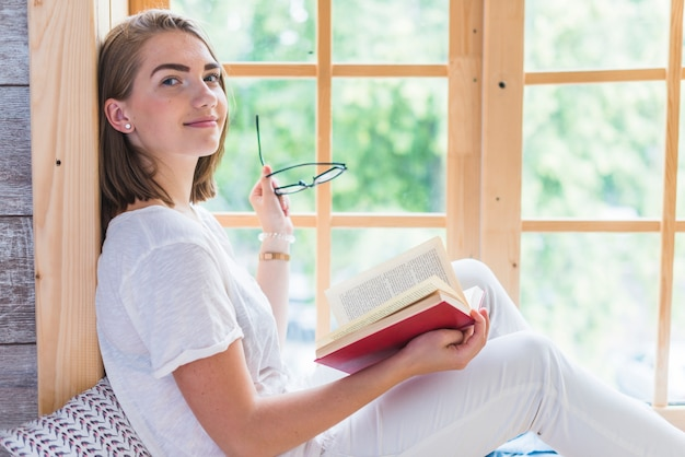 창문 가까이 안경과 책을 들고 젊은 여자의 모습