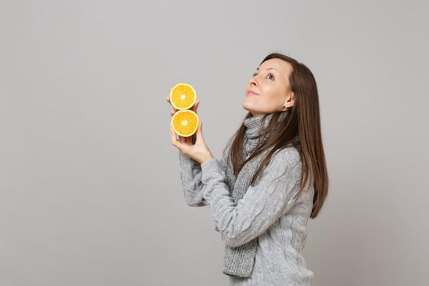 Вид сбоку молодой женщины в сером свитере, шарфе, глядя вверх, держа апельсины, изолированные на фоне серой стены. люди здорового образа жизни моды искренние эмоции, концепция холодного сезона. копируйте пространство для копирования.