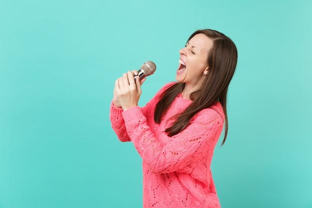 눈을 감고 니트 분홍색 스웨터를 입은 젊은 여성의 측면 보기, 파란색 벽 배경에 격리된 마이크에서 노래를 부르고 스튜디오 초상화. 사람들이 라이프 스타일 개념입니다. 복사 공간을 비웃습니다.