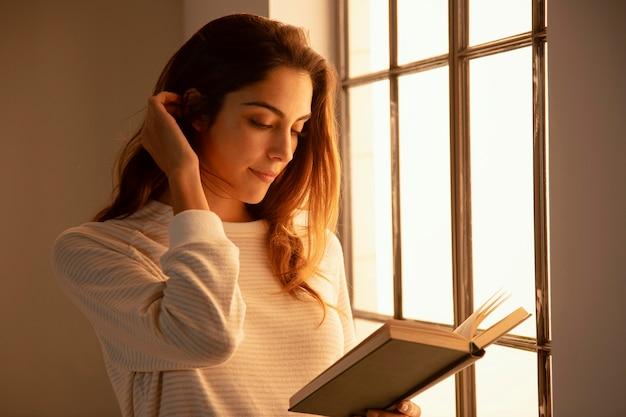 Вид сбоку молодой женщины, читающей книгу дома